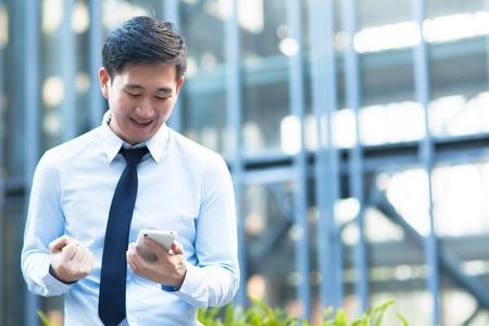Glücklicher asiatischer Geschäftsmann eine gute Nachricht erhalten