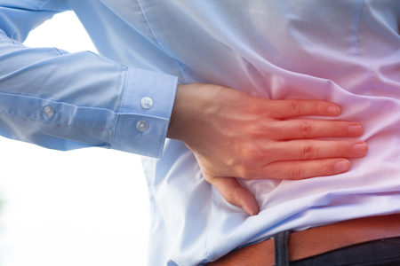 Hombre en uniforme de oficina que tiene la espalda tema del dolor / lesiones en la espalda Foto de archivo