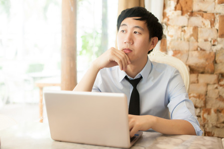 sit up: Young Asian casual businessman thinking while working in outdoor scene