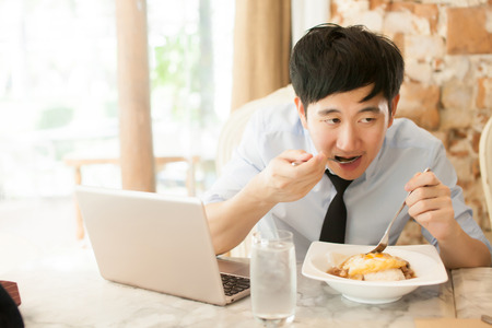 Young Asian man working while eating with his laptop in restaurant (selective focus)