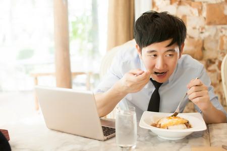 Jonge Aziatische man aan het werk tijdens het eten met zijn laptop in restaurant (selectieve aandacht) Stockfoto - 50919561