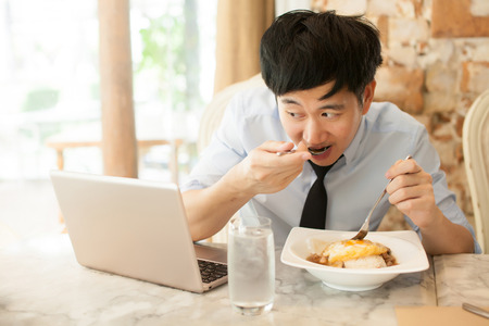 Young Asian man working while eating with his laptop in restaurant