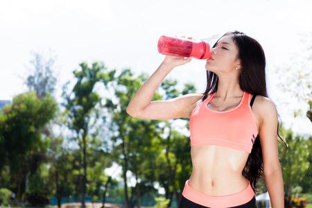アジア フィットネス女性飲料水またはプロテイン シェーク