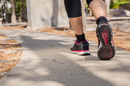 girl action: Running feet of young woman going by concrete trail in the park Stock Photo