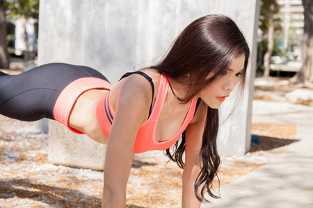 push: Young Asian fitness woman doing exercises in the park