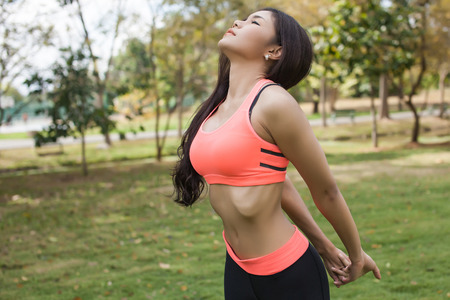 bra model: Asian Fitness Woman Stretching in the park
