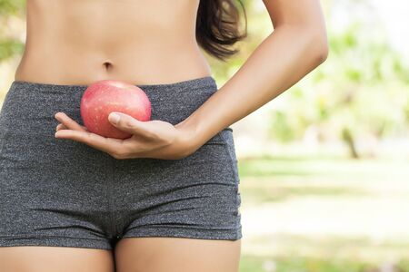 slim body: Healthy female holding apple at waist level outdoor in park Stock Photo
