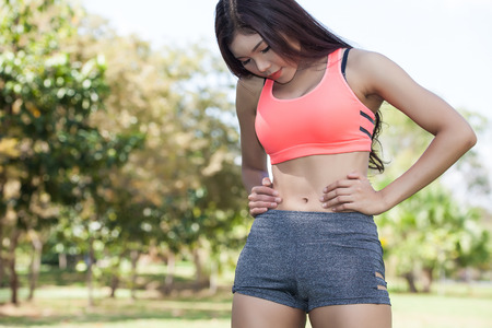 belly fat: Asian Woman in sport bra checking on her belly - fear of being fat Stock Photo