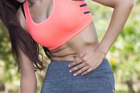 dolor abdominal: Mujer en sujetador deportivo que tiene una intoxicación de estómago  comida  problemas estomacales  problemas de útero  dolor de la menstruación Foto de archivo