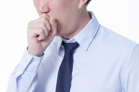Asian businessman suffering from a bad cough Stock Photo