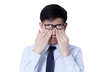 long hours: Young Asian businessman rubbing his tired eyes from long hours of works using computer