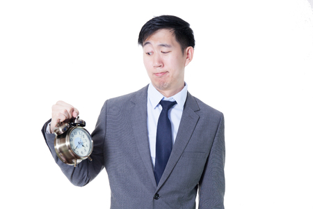 unpleasant: Young Asian businessman holding a clock in unpleasant face expression - business and time concept Stock Photo