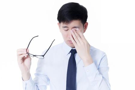 長い時間コンピューターを使用しての作品から彼の疲れ目をこすりながら若いアジア系のビジネスマン
