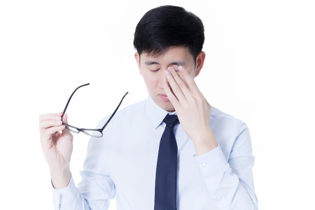 cansancio: Joven empresario asiático frotar los ojos cansados ??de las largas horas de trabajos que usan el ordenador Foto de archivo
