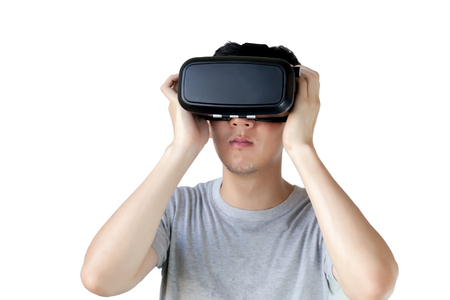 real world: Asian man wearing VR goggle and immersing himself in VR multimedia - in white isolated and clipping mask.  VR is simulation of a physical presence in places in the real world or an imagined world
