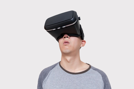 Asian man wearing VR goggle and immersing himself in VR multimedia in white isolated.