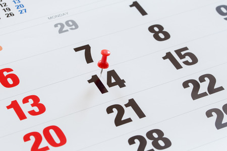 pushed: Pin pushed on a calendar concept for an important day.