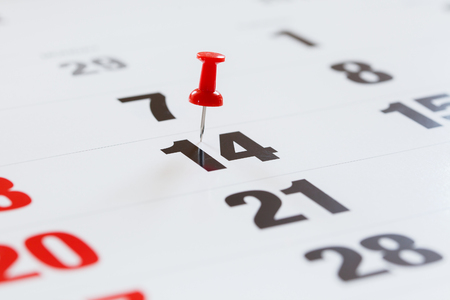 calendar date: Pin pushed on a calendar concept for an important day.