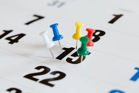 booked: Pushpins on calendar, Busy and overworking days. Important date or meeting appointment reminder concept. Stock Photo