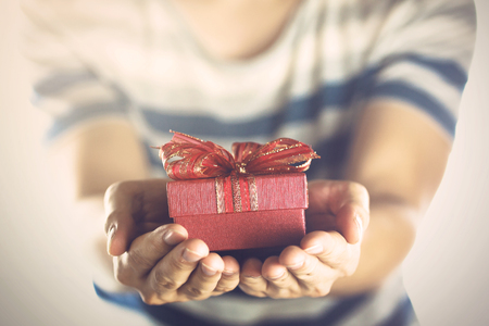 Young man giving and presenting a gift to someone.