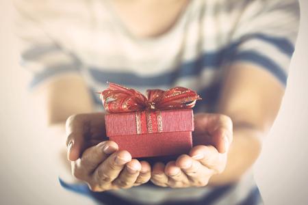 Junger Mann, und ein Geschenk für jemanden zu präsentieren.