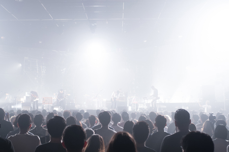 live band: Surprised music band crowds standing illuminated from stage lights. Stock Photo