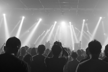 gig: Music concert crowds illuminated from stage lights (very shallow depth of field) - Black and White Stock Photo