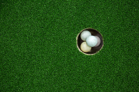 stacked up: Top view of golf balls stacked up in green field