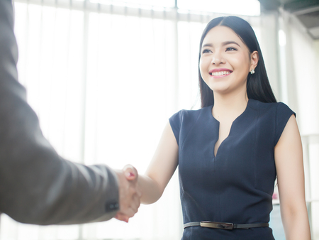 Smart and confident Asian businesswoman smiling and shaking hands 免版税图像