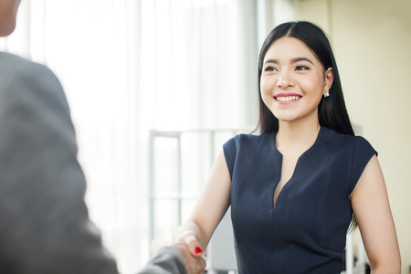Beautiful Asian businesswoman smiling and shaking hands with other businessman Banco de Imagens