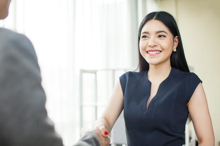 Piękny Azjatycki bizneswoman uśmiecha się ręki z innym biznesmenem i trząść Zdjęcie Seryjne