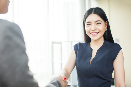 Beautiful Asian businesswoman smiling and shaking hands with other businessman Stock Photo