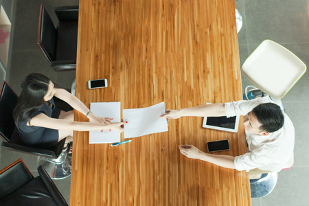 passing over: Top View of Business People sitting behind meeting desk, handing out documents Stock Photo