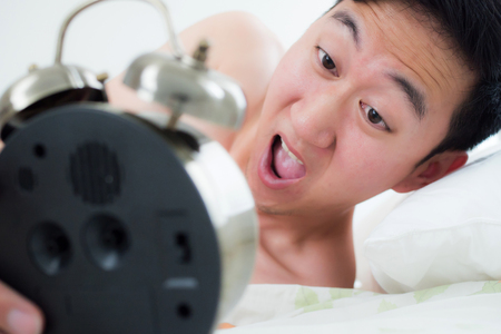 oversleep: Young man on his bedside, knowing that he overslept and late for his schedule Stock Photo