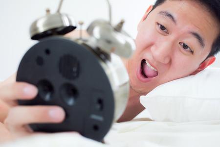 visage homme: Jeune homme sur son lit, sachant qu'il a dormi trop longtemps et � la fin de son emploi du temps