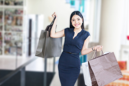 Asian woman taking a walk in the mall and holding a lot of shopping bags Banco de Imagens