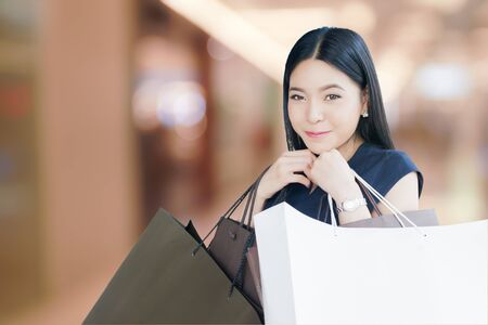 Asian happy shopaholic woman with loads of shopping bags in blurred mall background