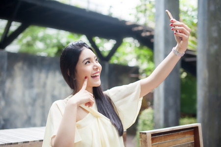 Asian woman taking a selfie with her phone in public park Reklamní fotografie