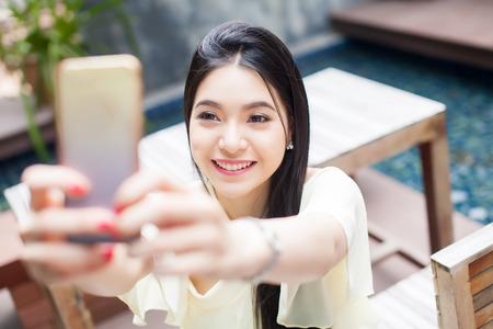 アジアの女性の公共の公園 (彼女の顔にフォーカス) で彼女の携帯電話で selfie を取って 写真素材