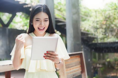 明るく幸せなアジアの女の子は、タッチ パッド タブレットを見て興奮してください。
