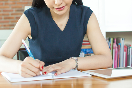 letter writing: Beautiful woman smiling and writing a notebook on table (Focus on Mouth)