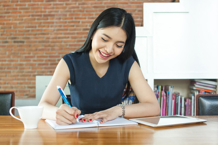 writing paper: Beautiful Asian woman smiling and writing a notebook on table Stock Photo