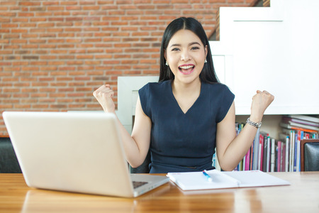 Excited Asian woman raising her arms while working on her laptop - success and business concept Stock Photo
