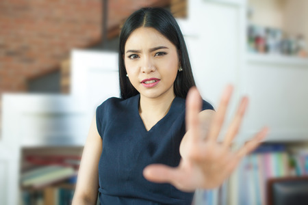 Asian woman with her hand signaling stop (only face is in focus) 스톡 콘텐츠