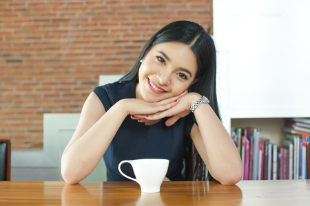 Asian Woman Smiling in front of coffee on the table Stock Photo
