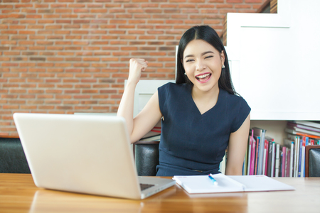 Excited Asian woman raising her arms while working on her laptop - success and business concept Banco de Imagens