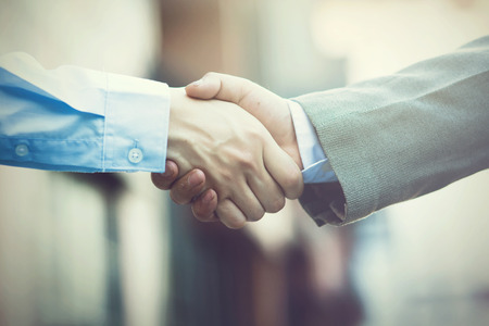 Business handshake. Two businessman shaking hands (Vintage tone) Standard-Bild