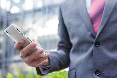 cellphone: Business man using a cellphone (focus on cellphone) Stock Photo