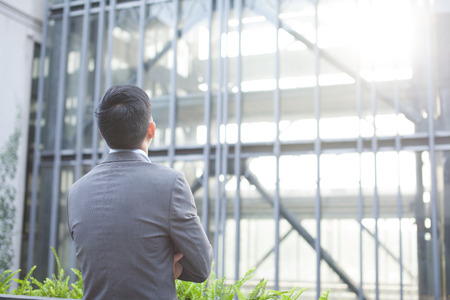 Ambitious business man from the back - looking at glass building (Shallow depth of field)