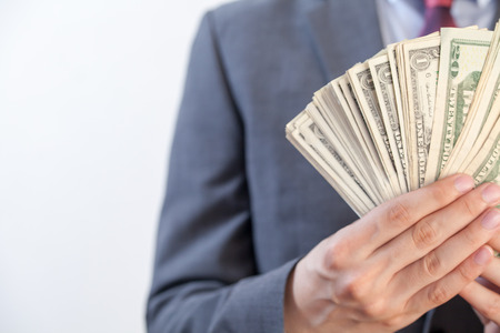 capitalist: Businessman holding bank notes in white isolated background with copyspace